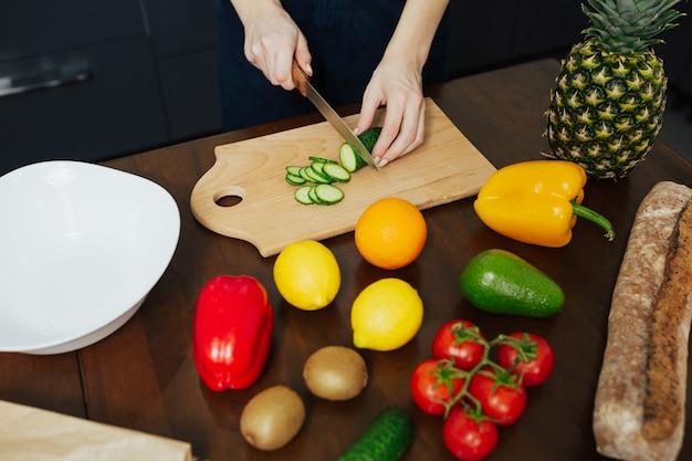 Le mani della donna tagliano il cetriolo, cucinando insalata fresca sana in cucina.