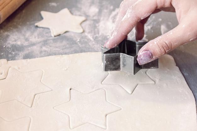 Mani della donna che tagliano la pasta con una teglia a forma di stella, da vicino