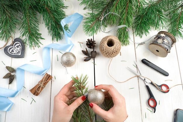Le mani di una donna decorano un ramo di pino sul tavolo.