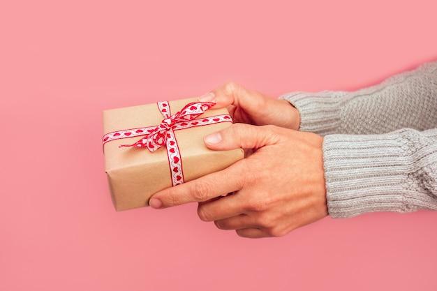 Le mani della donna che fanno un regalo con un fiocco di cuori su uno sfondo rosa. natale, capodanno, compleanno, san valentino, concetto di festa della mamma.