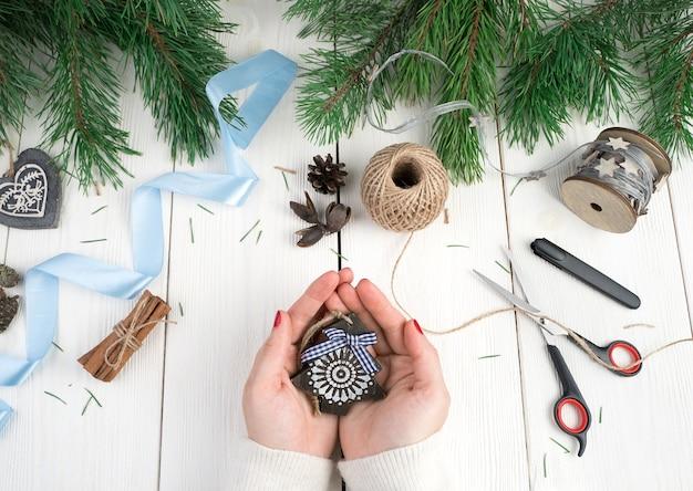 Le mani di una donna tengono un piccolo albero di natale in legno.