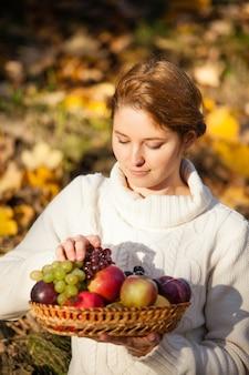 Le mani della donna che tengono un cesto con frutta fresca. avvicinamento