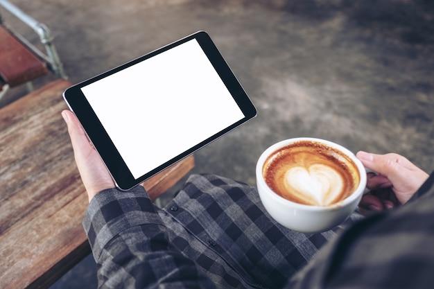 Mani della donna che tengono tablet pc nero con schermo vuoto mentre beve il caffè nella caffetteria