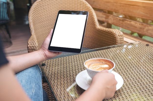Mani della donna che tengono tablet pc nero con schermo vuoto mentre beve il caffè nella caffetteria moderna