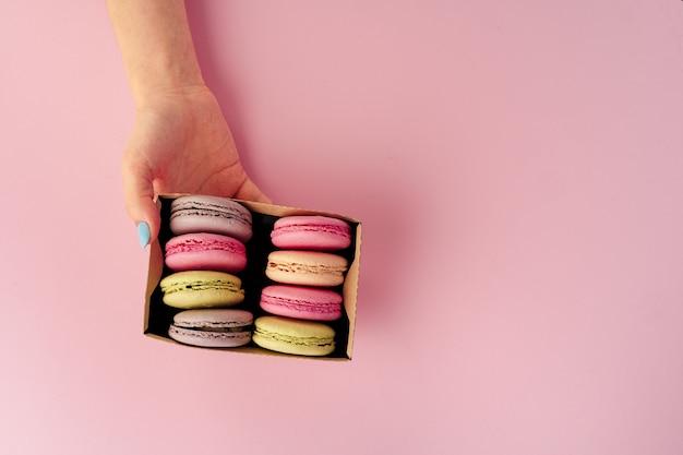 Mani della donna che tiene scatola con biscotti amaretti colorati, copia dello spazio