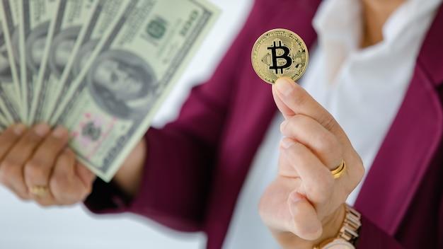 Le mani della donna che tengono la moneta criptata e diffondono il denaro delle banconote in dollari e il gesto di confronto concetto di investimento in risorse digitali e tesoro della vecchia scuola.