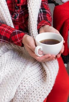 Mani della donna che tengono le tazze di tè o caffè vestite in vestiti festivi rossi e bianchi.