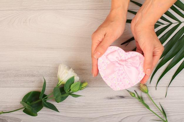 Le mani della donna che tengono una confezione regalo su fondo di legno grigio con bellissimi fiori e foglie verdi. concetto di fare un regalo nei giorni festivi. vista dall'alto.