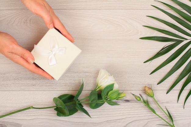 Le mani della donna che tengono una confezione regalo su fondo di legno grigio con bellissimi fiori e foglie verdi. concetto di fare un regalo in vacanza o compleanno. vista dall'alto.