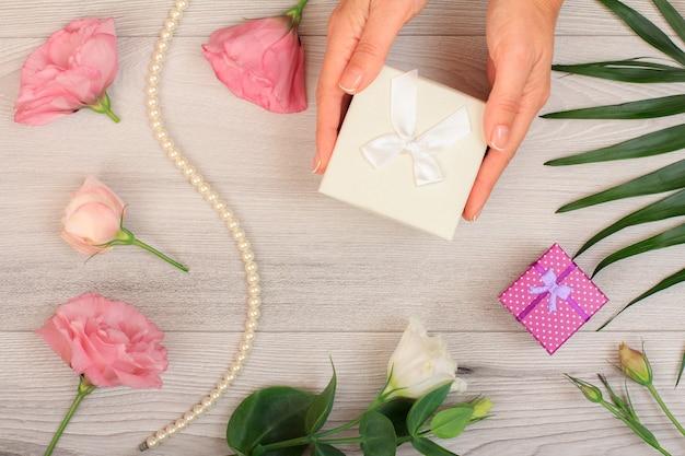 Le mani della donna che tengono una confezione regalo su fondo di legno grigio con bellissimi fiori e foglie verdi. concetto di fare un regalo il giorno di san valentino o il compleanno. vista dall'alto.