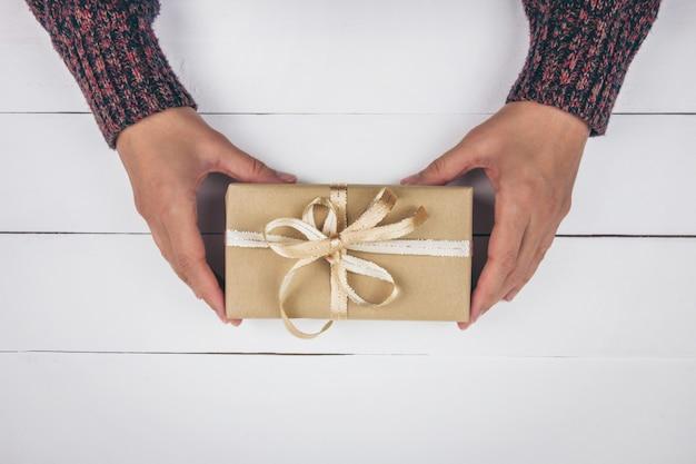 Le mani della donna che tengono un regalo con un fiocco dorato su fondo di legno bianco. natale, capodanno, compleanno, san valentino, concetto di festa della mamma. vista dall'alto.