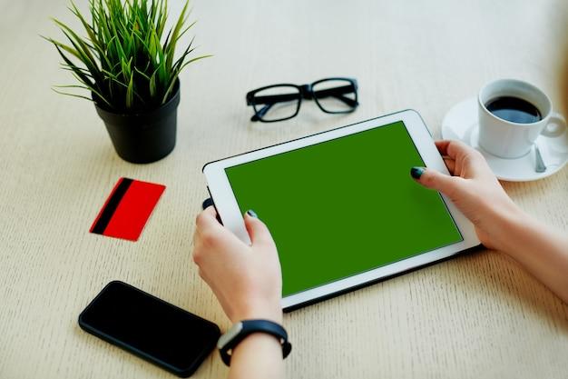 Mani della donna che tengono compressa verde, carta di credito, occhiali, telefono cellulare e tazza di caffè sul tavolo, concetto di freelance, shopping online.