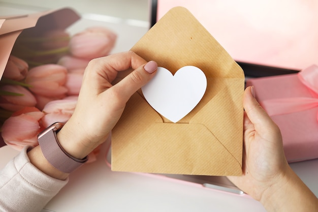 Le mani della donna che tengono una lettera in una busta artigianale. sfondo rosa, concetto di san valentino. fiore di tulipani e confezione regalo rosa sullo sfondo. scrivania da donna.