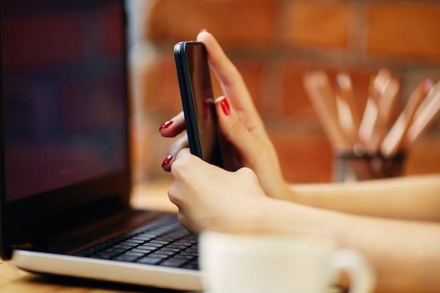 Mani della donna che tiene il telefono cellulare, seduto nella caffetteria con laptop e tazza di caffè, concetto di freelance, close up, manicure rossa.