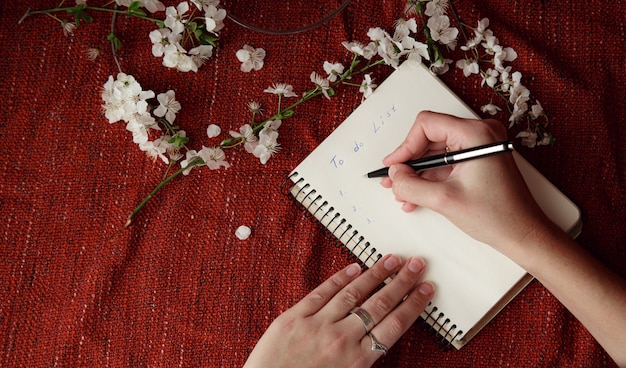 Le mani della donna che tengono penna e blocco note a spirale come mockup per il tuo design. sfondo rosso, stile piatto. idea e concetto di primavera, cambiamento, esprimere un desiderio e fissare obiettivi