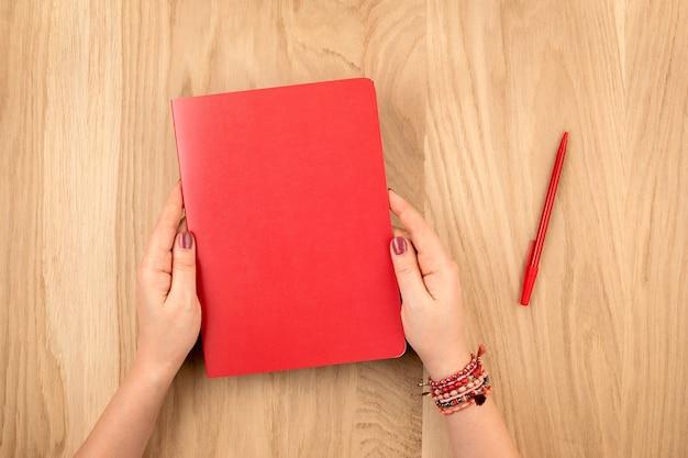 Mani della donna che tengono il diario personale per la progettazione sulla parete del desktop in legno, piatto laici