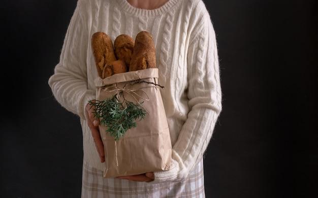 Mani della donna che tengono il sacchetto della spesa con pane per le vacanze di capodanno o natale