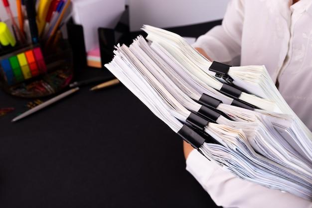 Mani della donna che tengono una pila di documenti