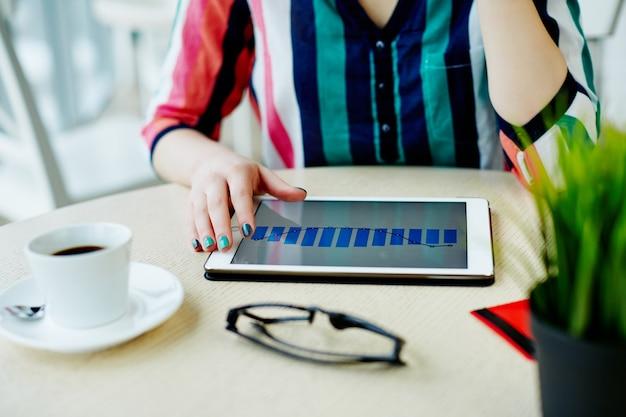 Mani della donna che tengono compressa con istogrammi, carta di credito, bicchieri e tazza di caffè sul tavolo, concetto di freelance, shopping online.