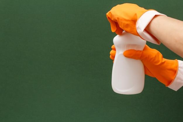 Le mani della donna in un guanto protettivo arancione stanno aprendo una bottiglia di detersivo per piatti su sfondo verde. concetto di lavaggio e pulizia.
