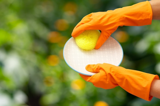 Le mani della donna in guanti protettivi arancioni con un piatto e una spugna sullo sfondo naturale sfocato. concetto di lavaggio e pulizia.