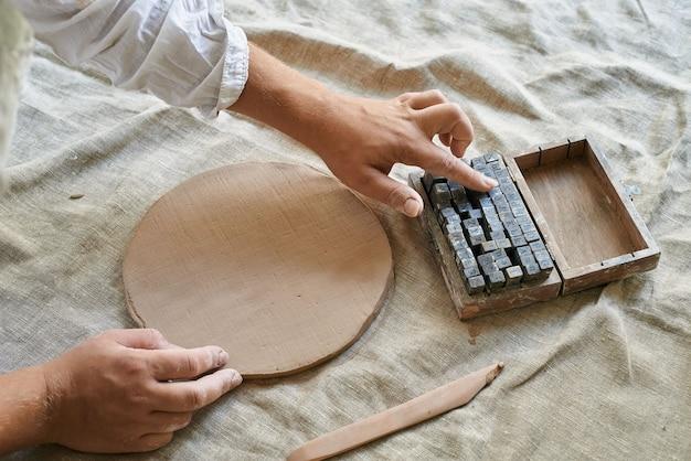 Le mani della donna raccolgono le lettere da stampare sull'argilla