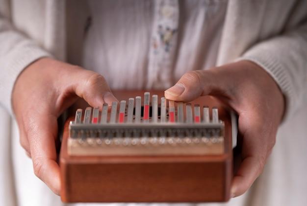 Mani della donna che giocano il kalimba Foto Premium