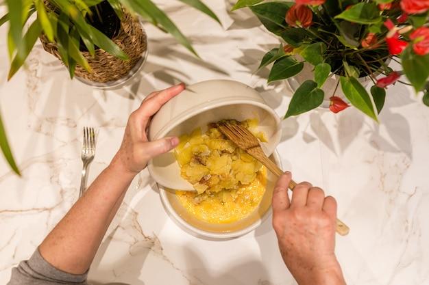 Mani della donna che versano le patate con la cipolla in una ciotola con le uova sbattute per cucinare una frittata di patate