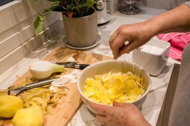 Mani della donna versando il sale sulle patate per cucinare una frittata di patate spagnola con cipolle