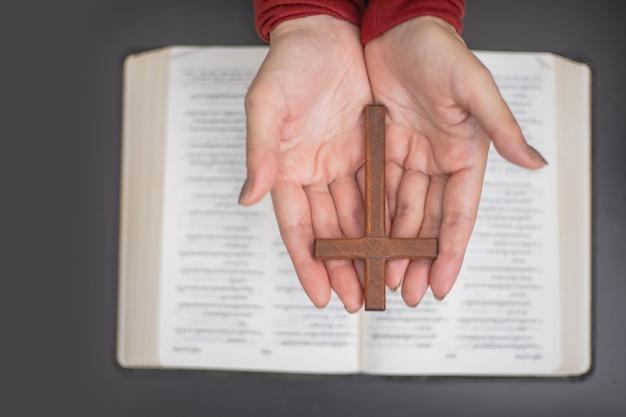 Mani di donna che pregano con una bibbia e una croce di legno