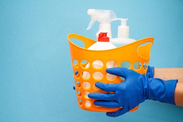 Le mani della donna in guanti protettivi di gomma che tengono cesto arancione con bottiglie di vetro e detergente per piastrelle su sfondo blu. concetto di lavaggio e pulizia.