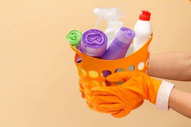 Le mani della donna in guanti protettivi di gomma che tengono cestino arancione con sacchetti della spazzatura, bottiglie di vetro e detergente per piastrelle, spugna su sfondo beige. concetto di lavaggio e pulizia.