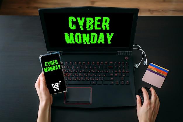 Mani della donna utilizzando laptop e smartphone per lo shopping online a casa durante i saldi del cyber monday. vista dall'alto dell'area di lavoro su sfondo nero
