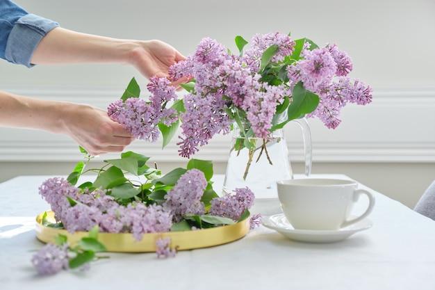Mani della donna con bouquet di fiori lilla in brocca di vetro sul tavolo bianco con tazza di tè