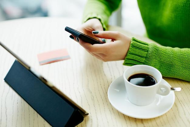 Mani della donna con manicure scura che tiene telefono cellulare, carta di credito, tablet e tazza di caffè sul tavolo, concetto di freelance, shopping online, piatto laici.