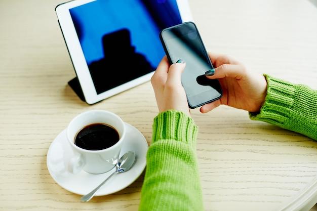 Mani della donna con manicure scura che tiene telefono cellulare, tablet e tazza di caffè sul tavolo, concetto di freelance, shopping online, piatto laici.
