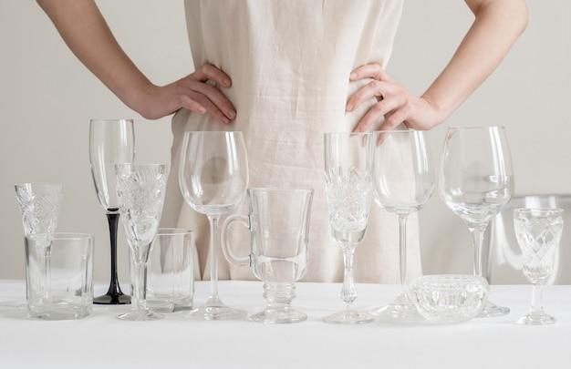 Le mani della donna con vetri di vino differenti sulla tavola sul bianco