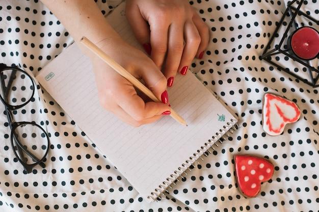 Mani della donna con manicure perfetta che tiene matita e blocco note a spirale