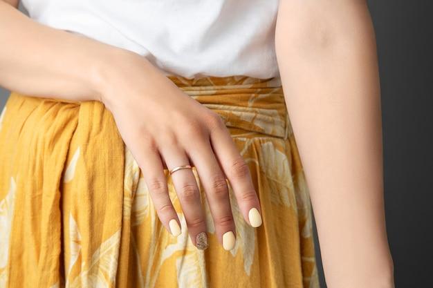 Mani di donna con unghie gialle lucide.