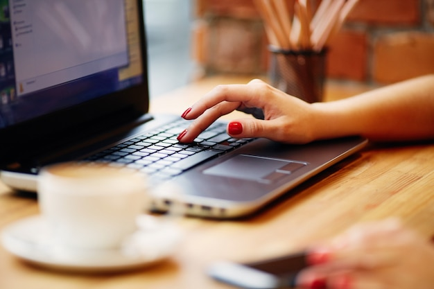 Mani della donna che lavorano con il computer portatile e il telefono cellulare, seduto nella caffetteria con una tazza di caffè, concetto di freelance, primi piani.