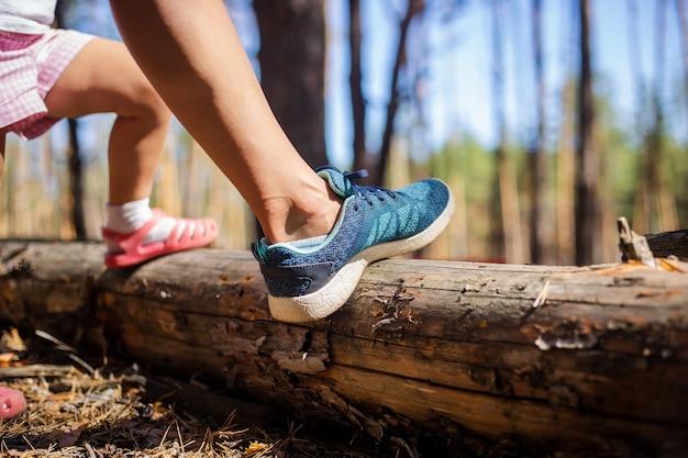 La gamba della donna e la gamba di un bambino sullo sfondo della foresta. escursionismo, bosco con fam.