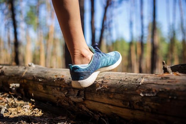 Gamba di donna in una scarpa da ginnastica durante le escursioni nella foresta. escursione in montagna, foresta.