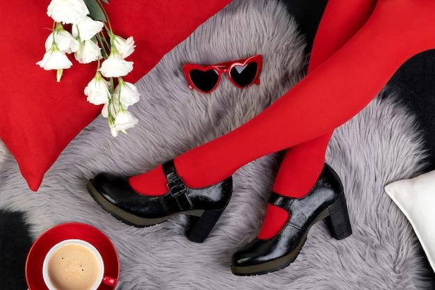 Gambe della donna in scarpe alla moda con occhiali da sole e fiori sulla superficie pelosa grigia