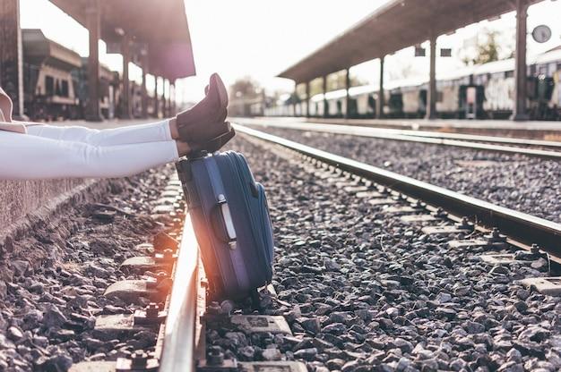 Gambe della donna che si appoggia su una valigia in una stazione ferroviaria al tramonto.