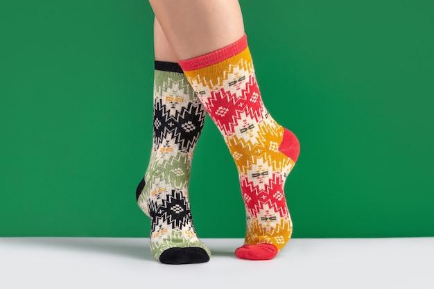 Gambe di donna in calzini lavorati a maglia multicolore con ornamento