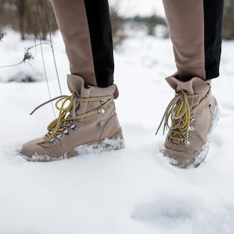 Le gambe della donna in pantaloni alla moda in stivali di moda in pelle marrone inverno sulla neve. avvicinamento.