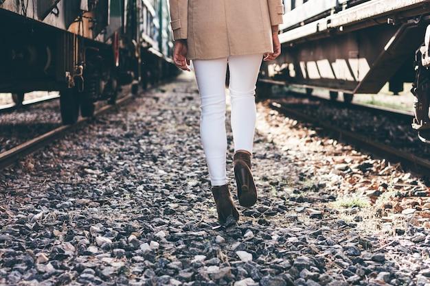Gambe di donna che camminano tra due vagoni ferroviari abbandonati.