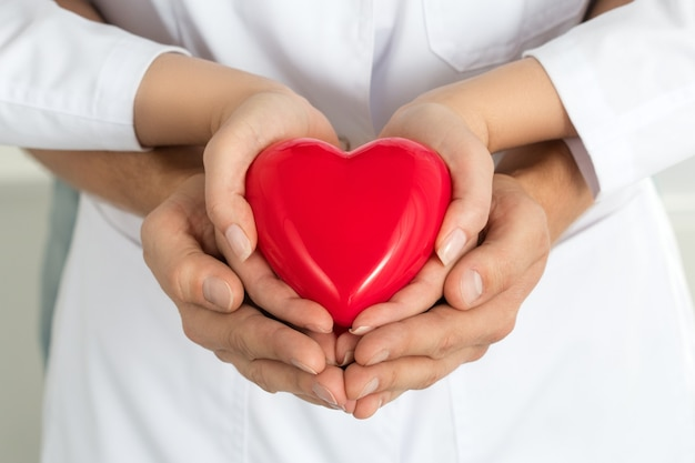 Mani dell'uomo e della donna che tengono insieme cuore rosso. amore, assistenza e concetto di assistenza sanitaria