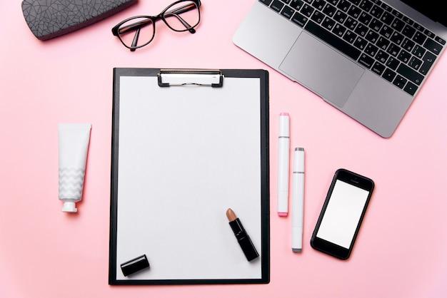 La scrivania rosa della donna con il foglio di carta pulito con lo spazio della copia libera, il computer portatile, il telefono con lo schermo bianco in bianco, una crema, il rossetto, gli occhiali e rifornisce il fondo.