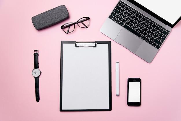La scrivania rosa della donna con il foglio di carta pulito con lo spazio della copia libera, il computer portatile, il telefono con lo schermo bianco in bianco, i vetri e rifornisce il fondo.